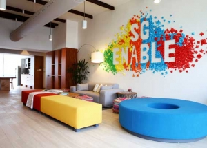 Interior of the SG Enable Office. A wall is decorated with vibrantly coloured paper decorations created by SG Enable staff.