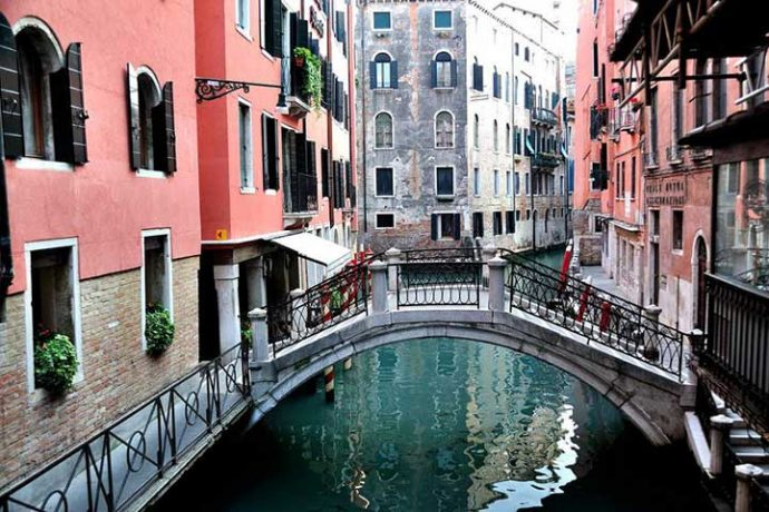 Bridge with steep stairs across a scenic canal at Venice