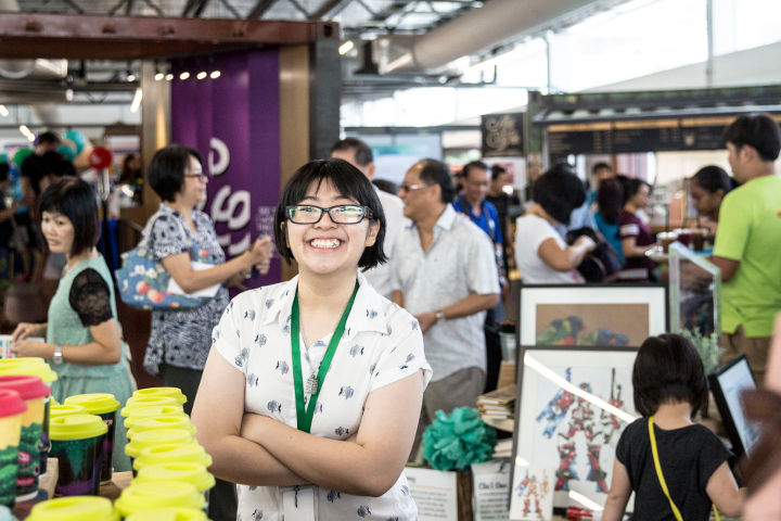 Photo of Catherine Tang, Assistant Retail Executive at The Art Faculty, standing in the backdrop of hustle at the Action for Autism mini-carnival 2016