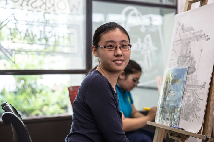 Photo of Selena Seow, 19, sitting at an easel at The Art Faculty. She is an artist with Pathlight School's Artist Development Programme.