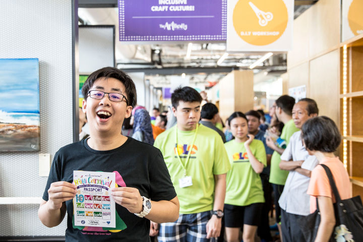 Photo of Ng Li Jie, 19, who used to be President of Pathlight School's student council. He stands in a crowded Art Faculty holding up a carnival passport from the Action for Autism mini-carnival event.