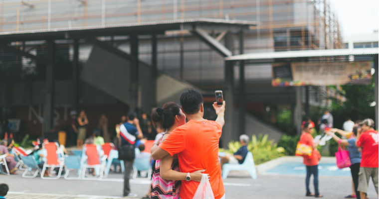 A couple shares a selfie in the middle of the Farmer's Market compound at the Enabling Village