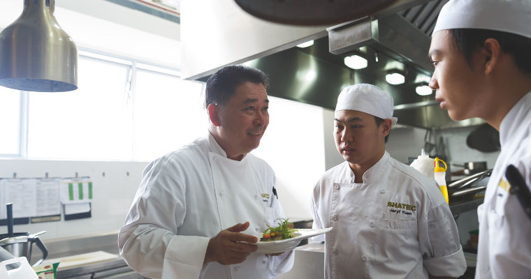 Chef Edmund Toh briefs two students at The Sapling's training kitchen