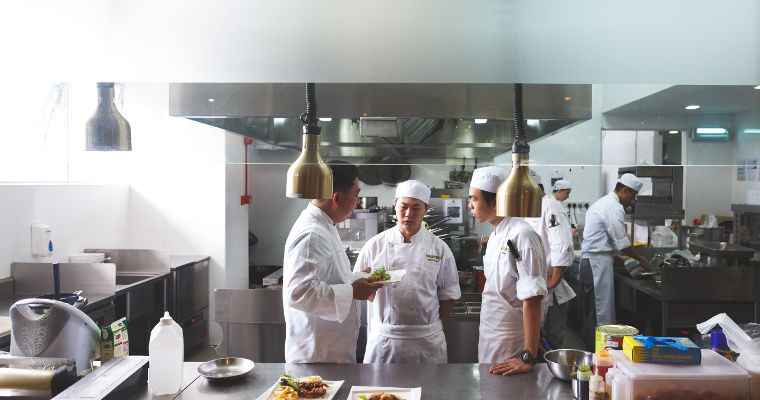 A chef trainer briefs students at the kitchen serving counter of The Sapling restaurant