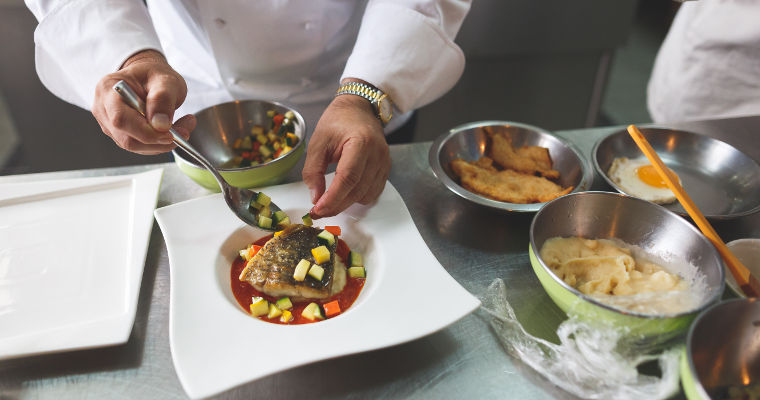 A chef lays out a fish dish with hands and a spoon