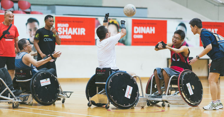 Participants at a wheelchair rugby workshop practice passing balls between themselves