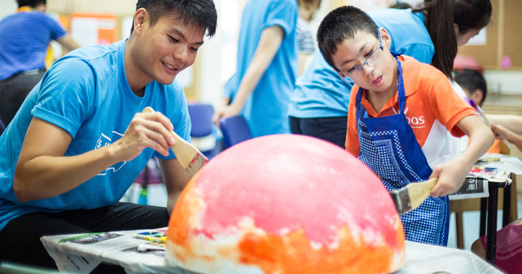 Hong Shin, 36, applies paints to a balloon with Mohamed Aiman, 12.
