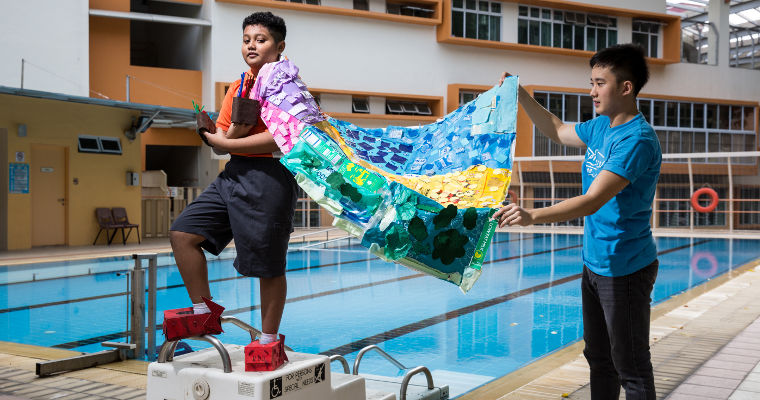 Ignatius Amos, 23, helps Muhammad Ryyan Zufayri, 12, position his multicoloured cape