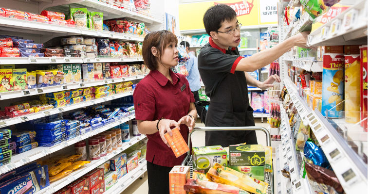 Photo of Qi Yao and Meei Lee working together to restock shelves at the supermarket