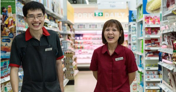 Qi Yao and Mei Ling, staff at the NTUC Fairprice supermarket located at the Enabling Village, posing for the camera