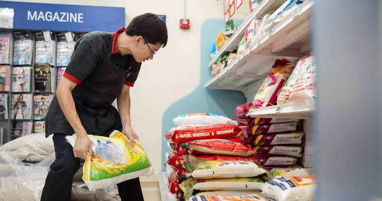 Photo of Qi Yao stacking packets of rice at the NTUC Fairprice supermarket outlet at the Enabling Village. Qi Yao has autism, and works and trains at the supermarket.