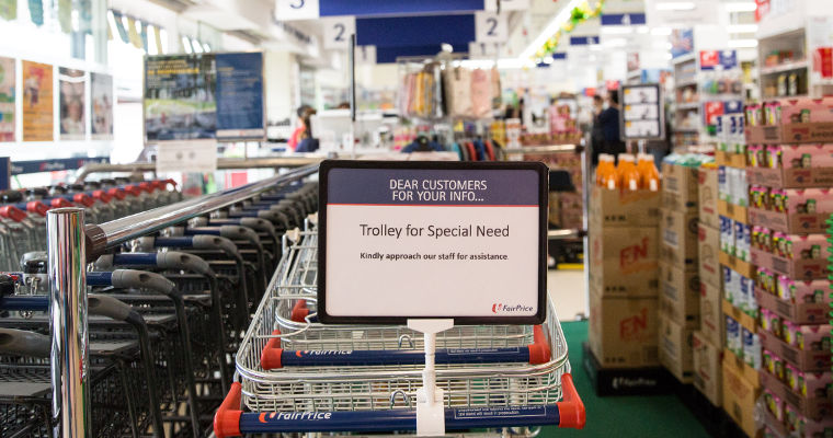 "Photo of a sign, ""Trolley for Special Needs"", attached to a column of special shopping trolleys designed to be attached to wheelchairs"
