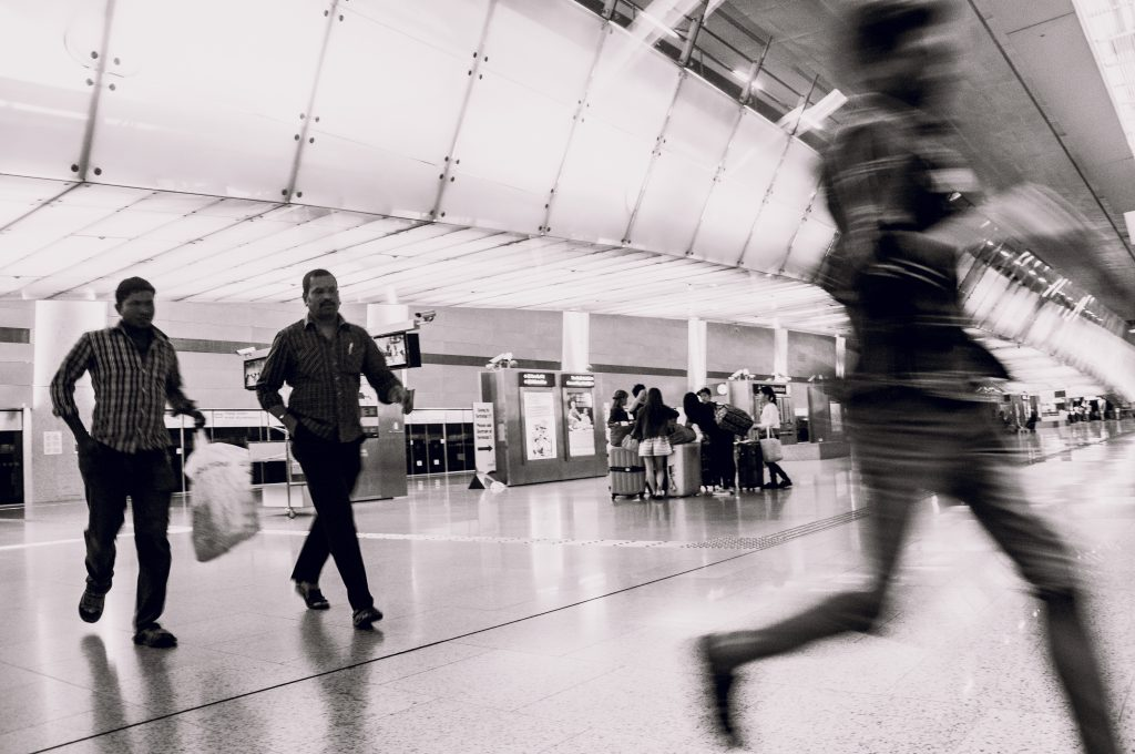 Black and white photo of passengers rushing across an MRT train platform to catch a train