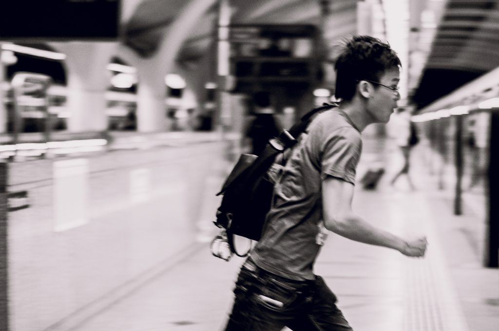 Black and white photo of a young man rushing on an MRT platform for a train.