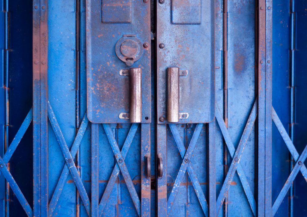 Colour photo of a pair of iron shutters. The gates, painted blue, are rusted in many areas.