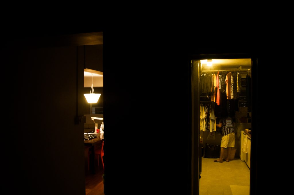Photo of a darkened room, leading to two open, lighted doorways. A person can be partially seen in one of the doorways, which appears to be a walk-in wardrobe