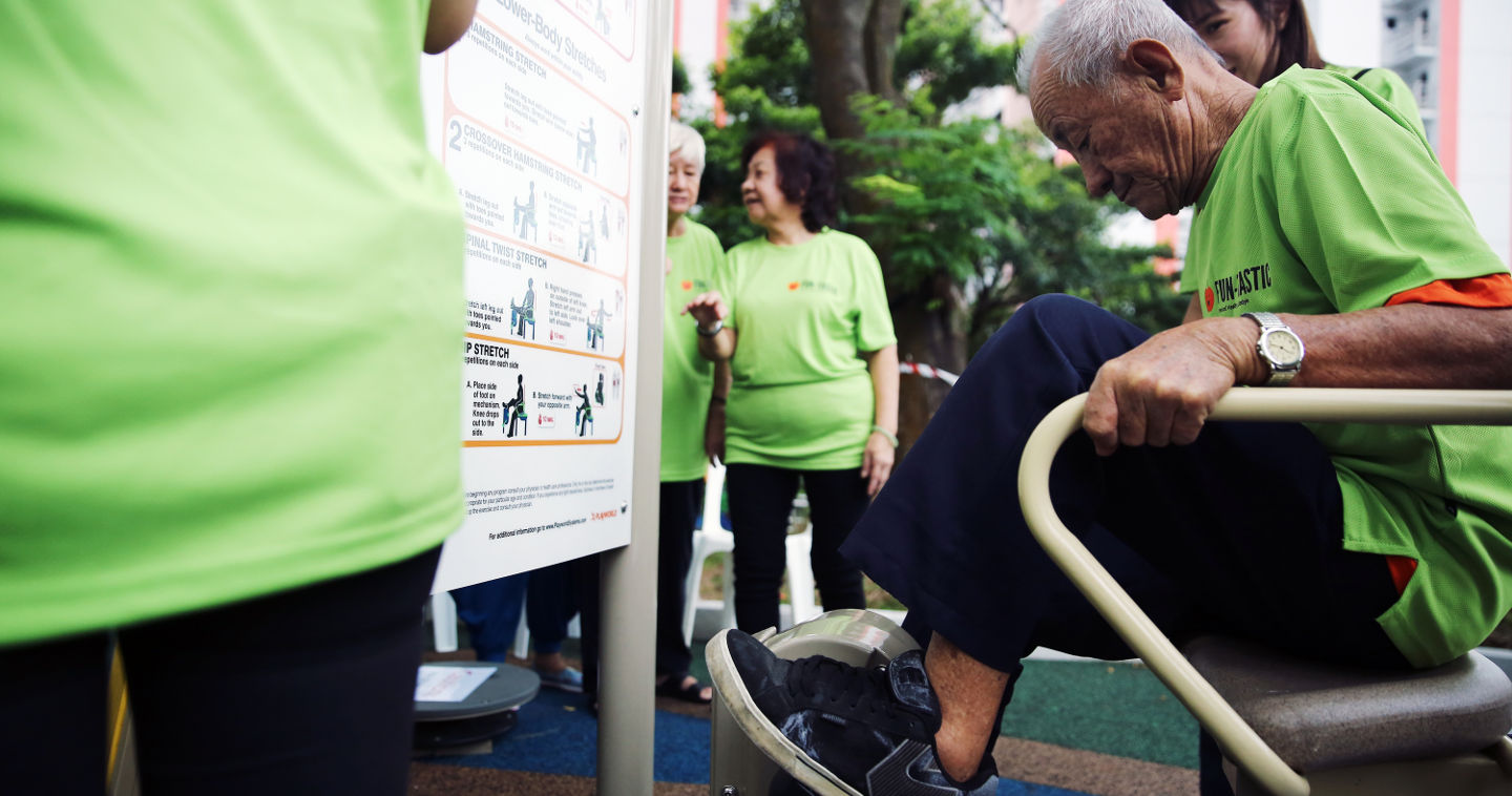 Seniors take turns to try out the outdoor fitness equipment at the Enabling Village, such as this cycling machine