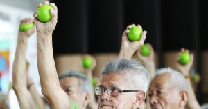 Participants at the Fun-Tastic programme for seniors warm up by squeezing stress balls above their heads
