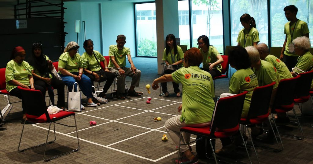 Seniors play team tic-tac-toe using bean bags and a large game board on the event hall floor