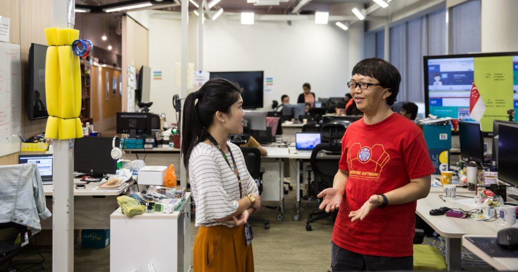 Photo of Zui Young chatting with a colleague against the backdrop of his open workplace