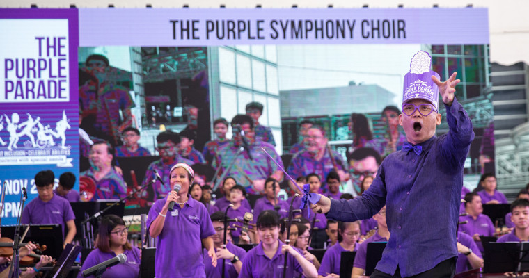 Mr Quek Ling Kiong of the Purple Symphony encouraging the audience to clap along. Wan Wai Yee, the visually impaired lead singer for the item, is in the background.