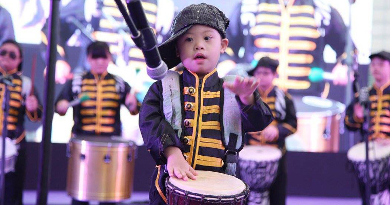 Photo of a drummer performing on stage as part of the Down Syndrome Association Drum Prodigy Ensemble