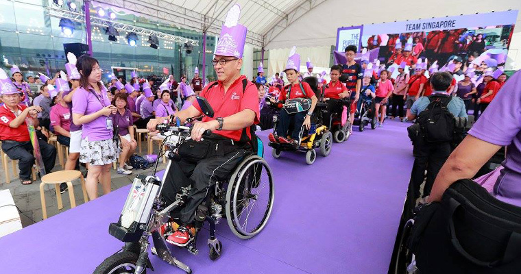 Photo of the Team Singapore contingent rolling off the stage in their wheelchairs