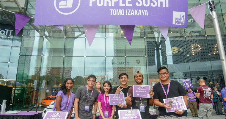 Photo of volunteers at the Tomo Izakaya stall at the Purple Parade carnival. The stall is selling purple sushi,
