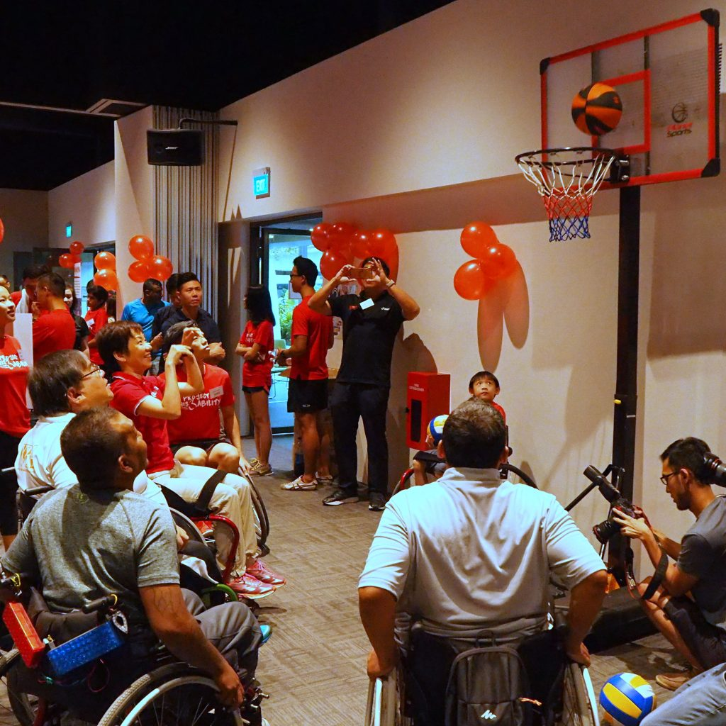 Photo of Minister Grace Fu shooting a basketball while seated in a wheelchair