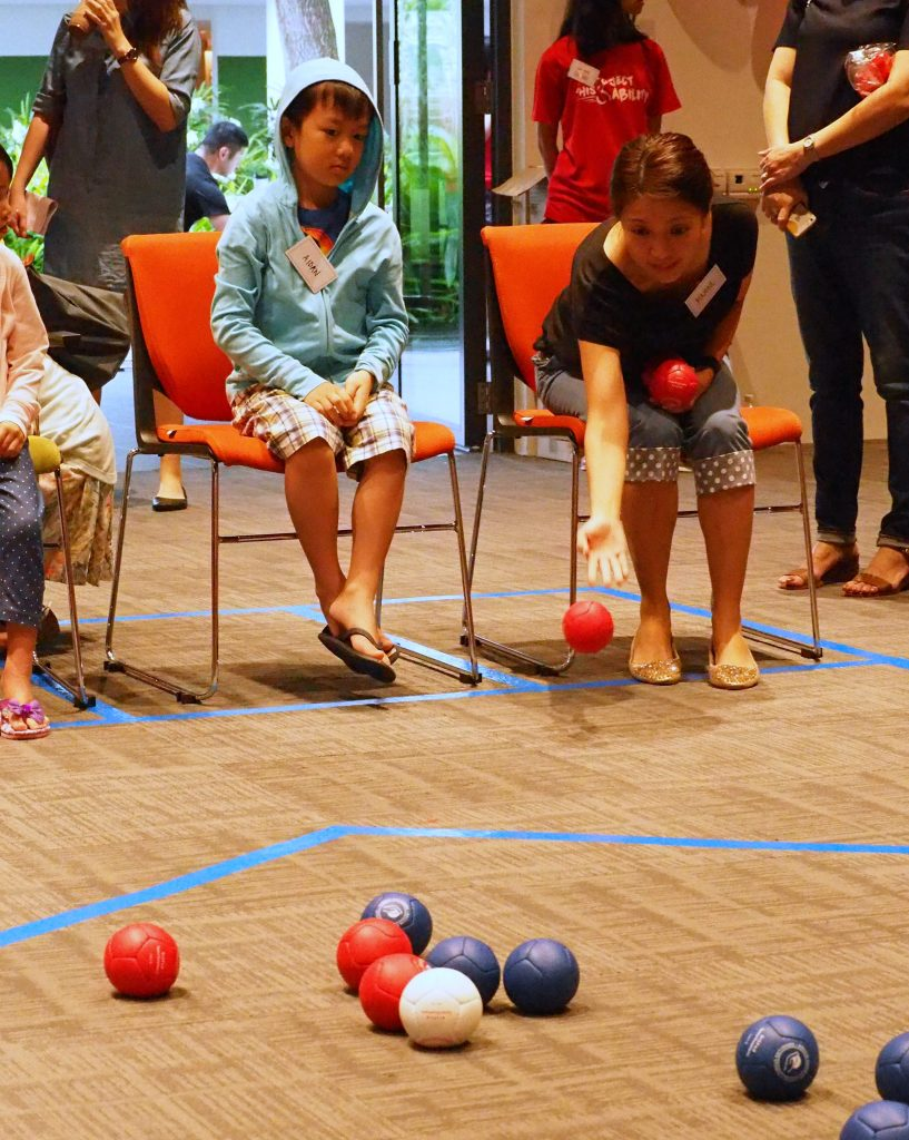 Photo of mother playing a game of Boccia against his son