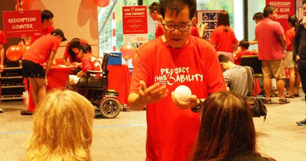 Photo of a volunteer explaining the rules of Boccia to participants