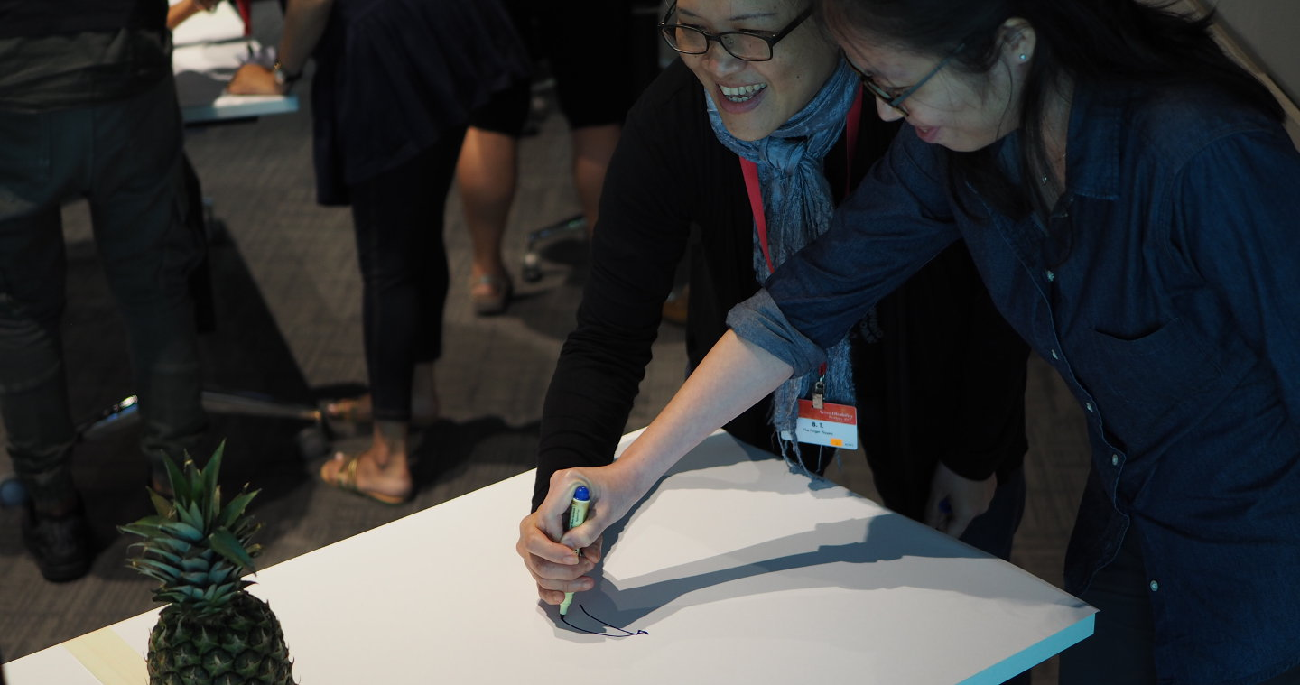 Two participants at the 2017 Arts and Disability Forum attempt to draw a pineapple with one pen, without communicating to each other