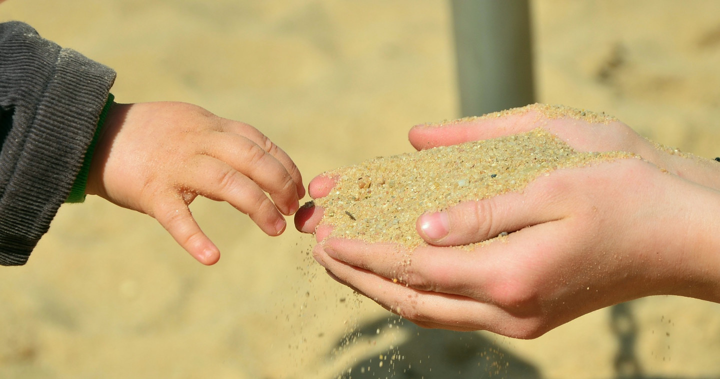 Photo of a woman's cupped hands passing sand to a child
