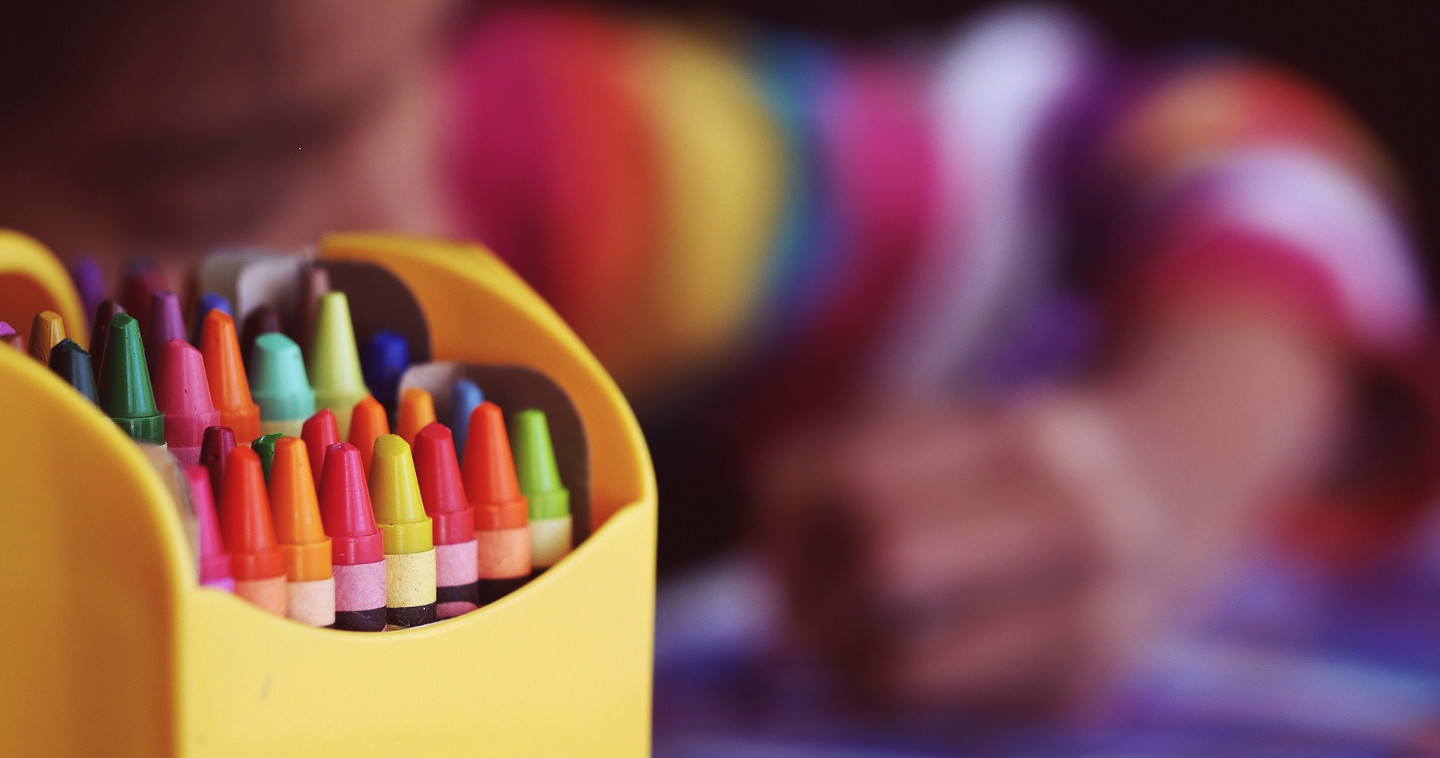 Photo of a child with a box of colourful crayons