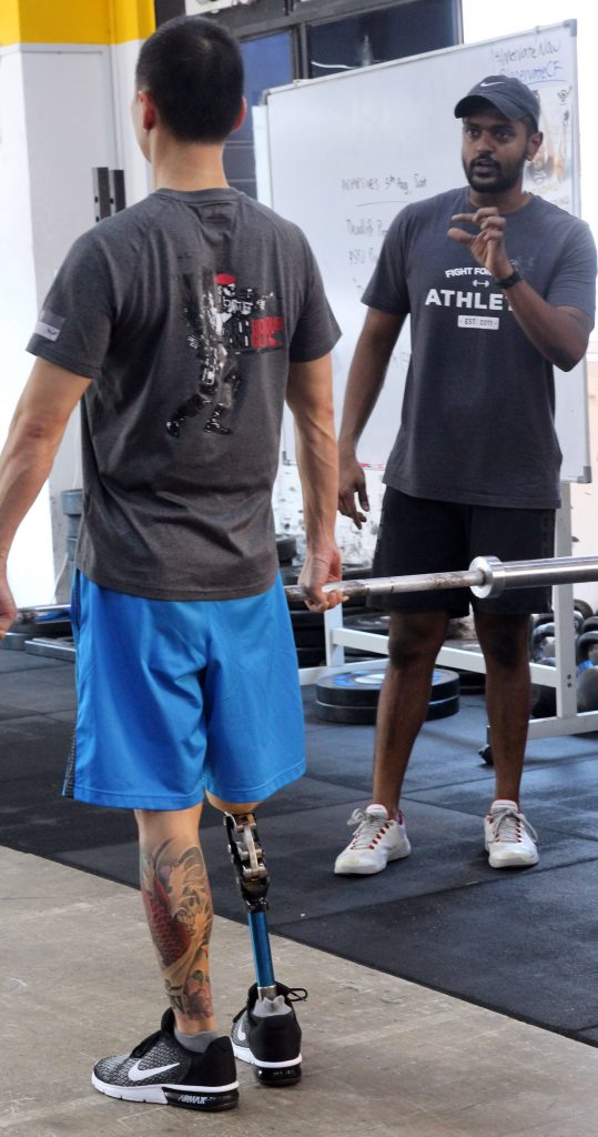 Photo of Moses James with a client at an Adaptive CrossFit session
