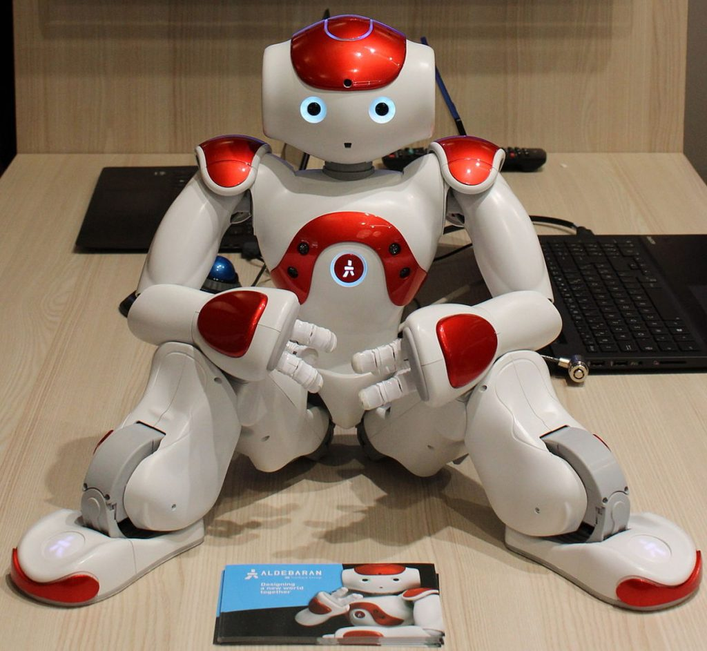 The NAO robot from Softbank Robotics, seated on a desk. (