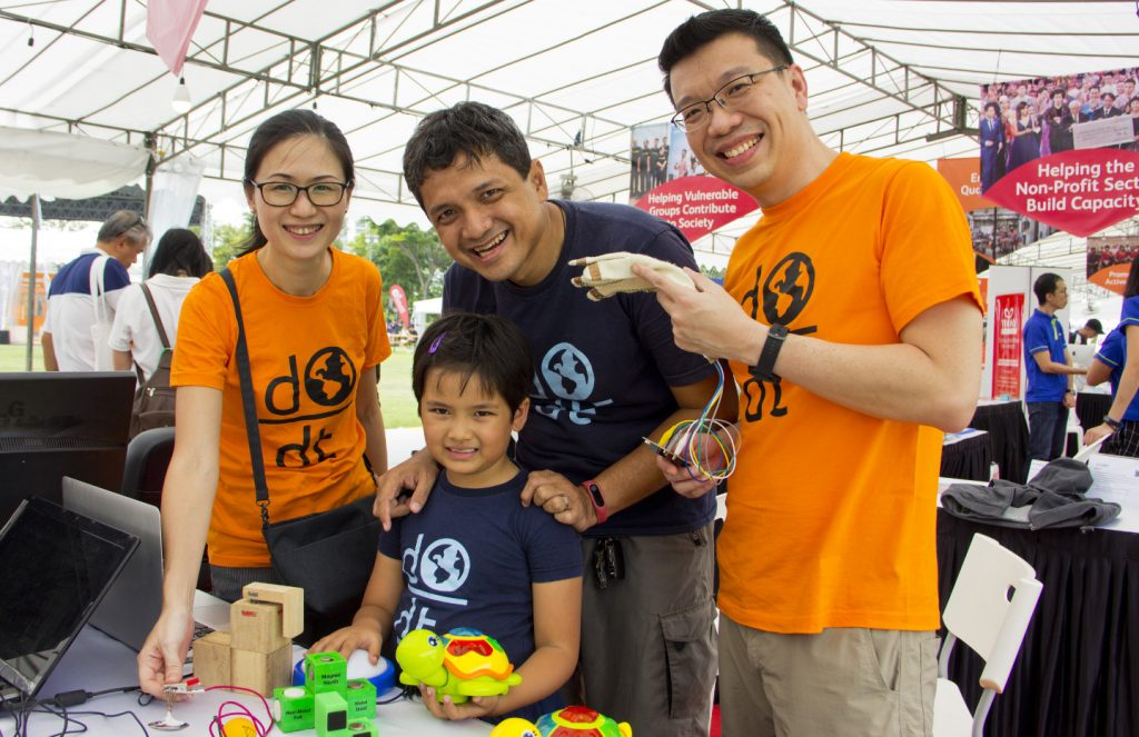 Photo of Volunteers at the Engineering Good booth, holding up toys that have been modified for accessibility
