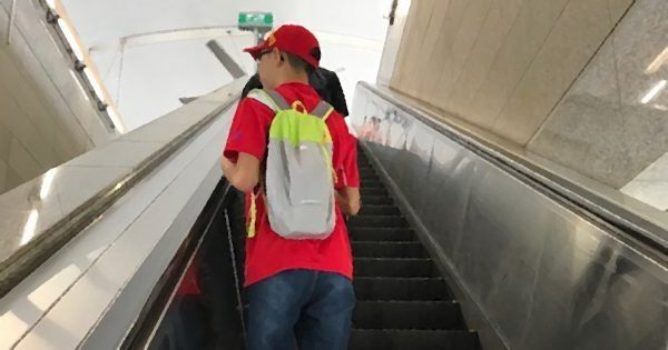Photo of an independent travelling project participant riding an escalator at an MRT station