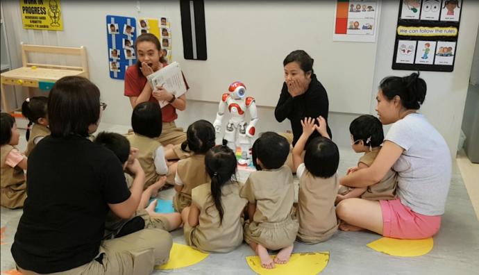 Children at the Kindle Garden preschool gather around the robot Nao for a round of storytelling