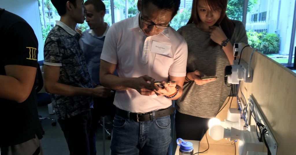 Photo of participants looking at smart lamps at a smart home workshop conducted at the Enabling Village