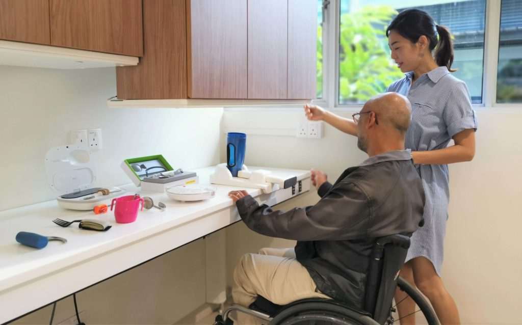 A male wheelchair user trying out a height-adjusted table with the help of a female companion.