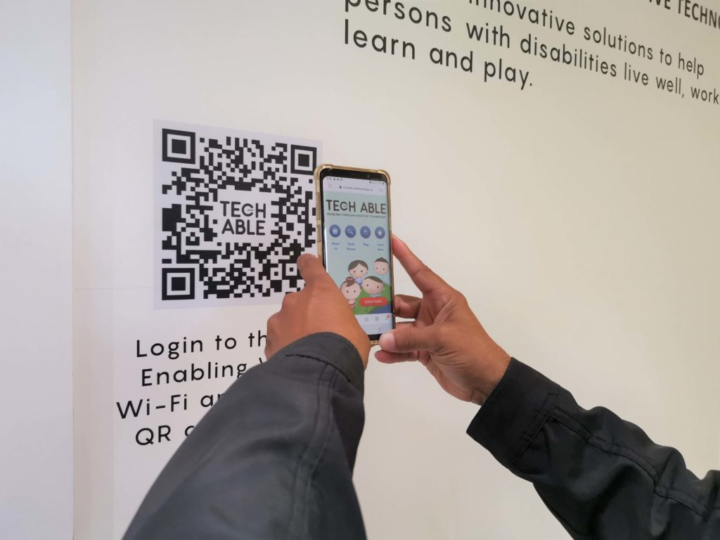 A visitor scans the QR code on the wall to launch the interactive web app which contains information about the assistive technology devices on display.