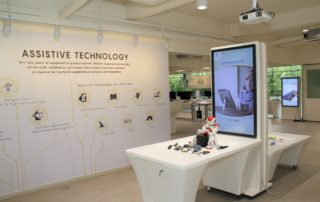 Interior of Tech Able showing digital screens and some assistive technology devices on display like a robot for self-exploration.