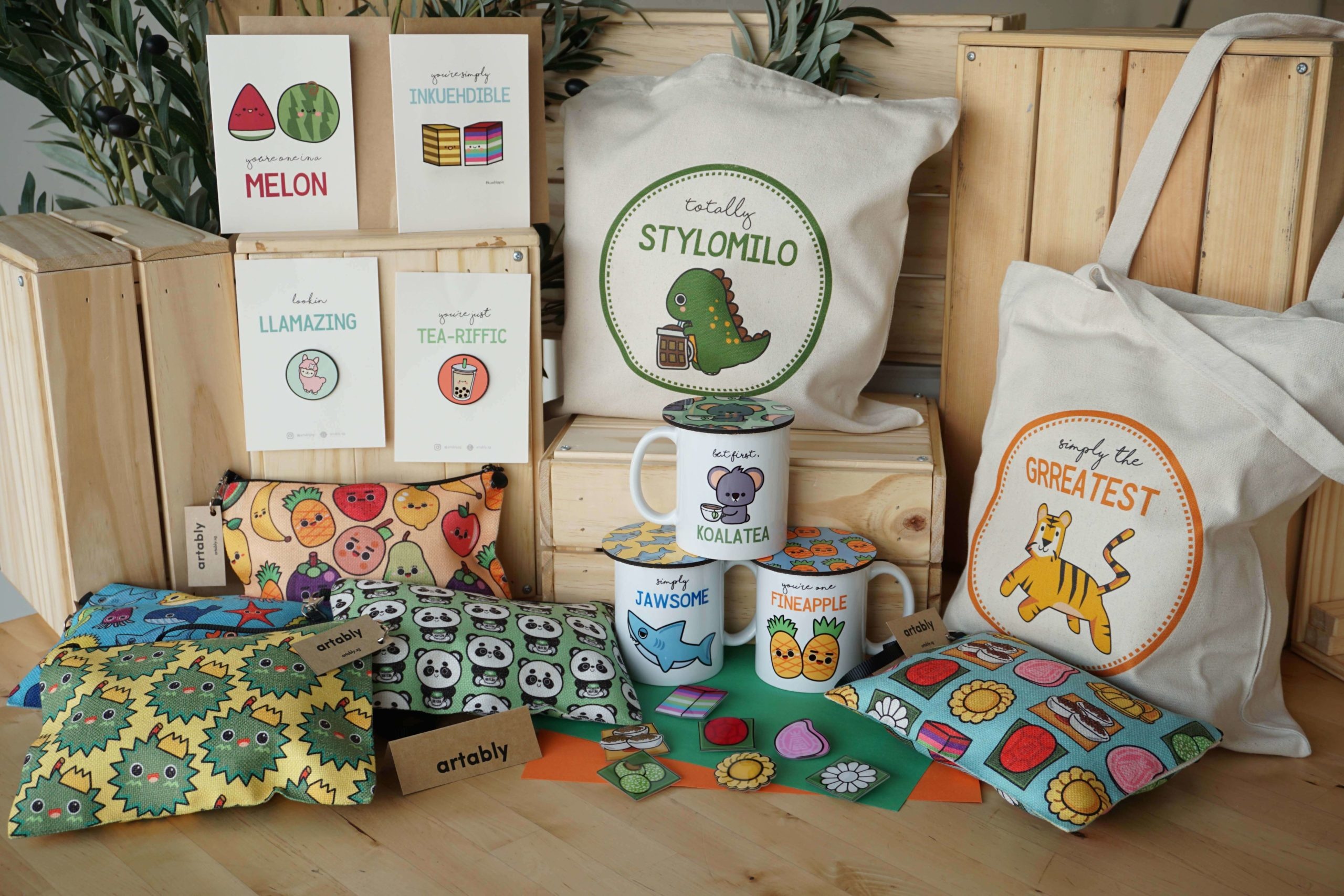 Some examples of Junior Art Lab's merchandise - including tote bags and mugs - featuring their creative and whimsical designs.